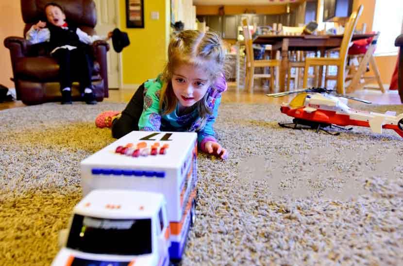 کودک در حال بازی با ماشین اورژانس بازی